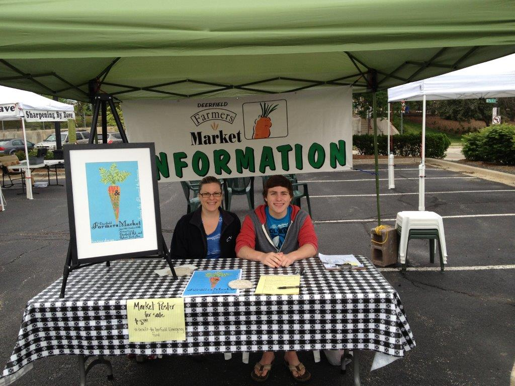 Two people sitting at informational booth at market