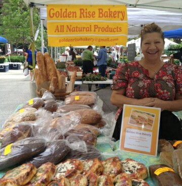 Golden Rise Bakery farmers stand with loaves of bread