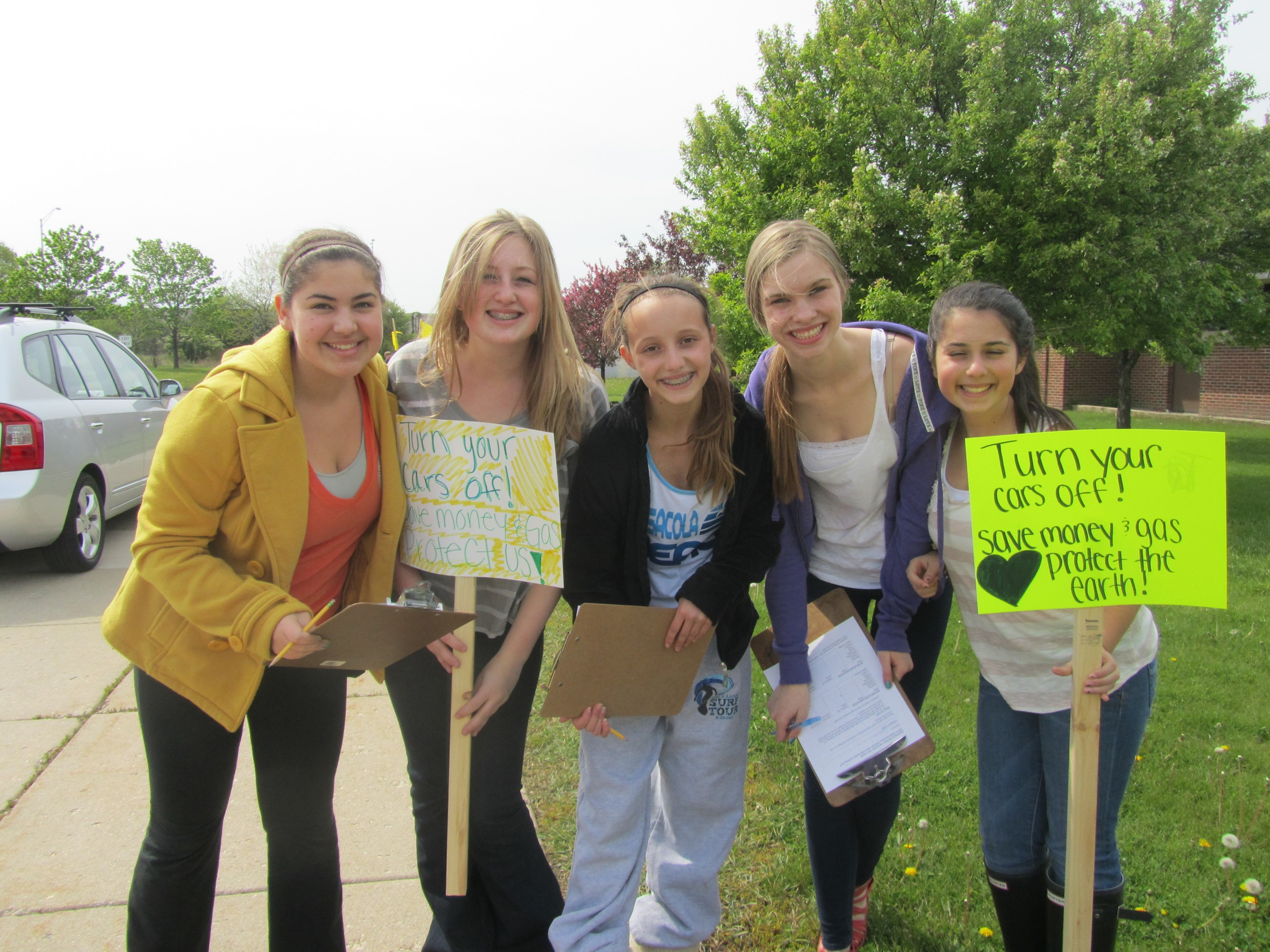 Five girls holding signs outside