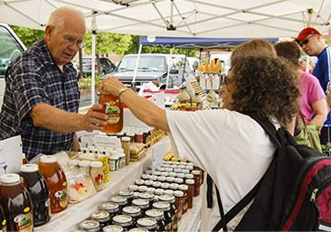 Man selling a woman some honey at the Farmers Market