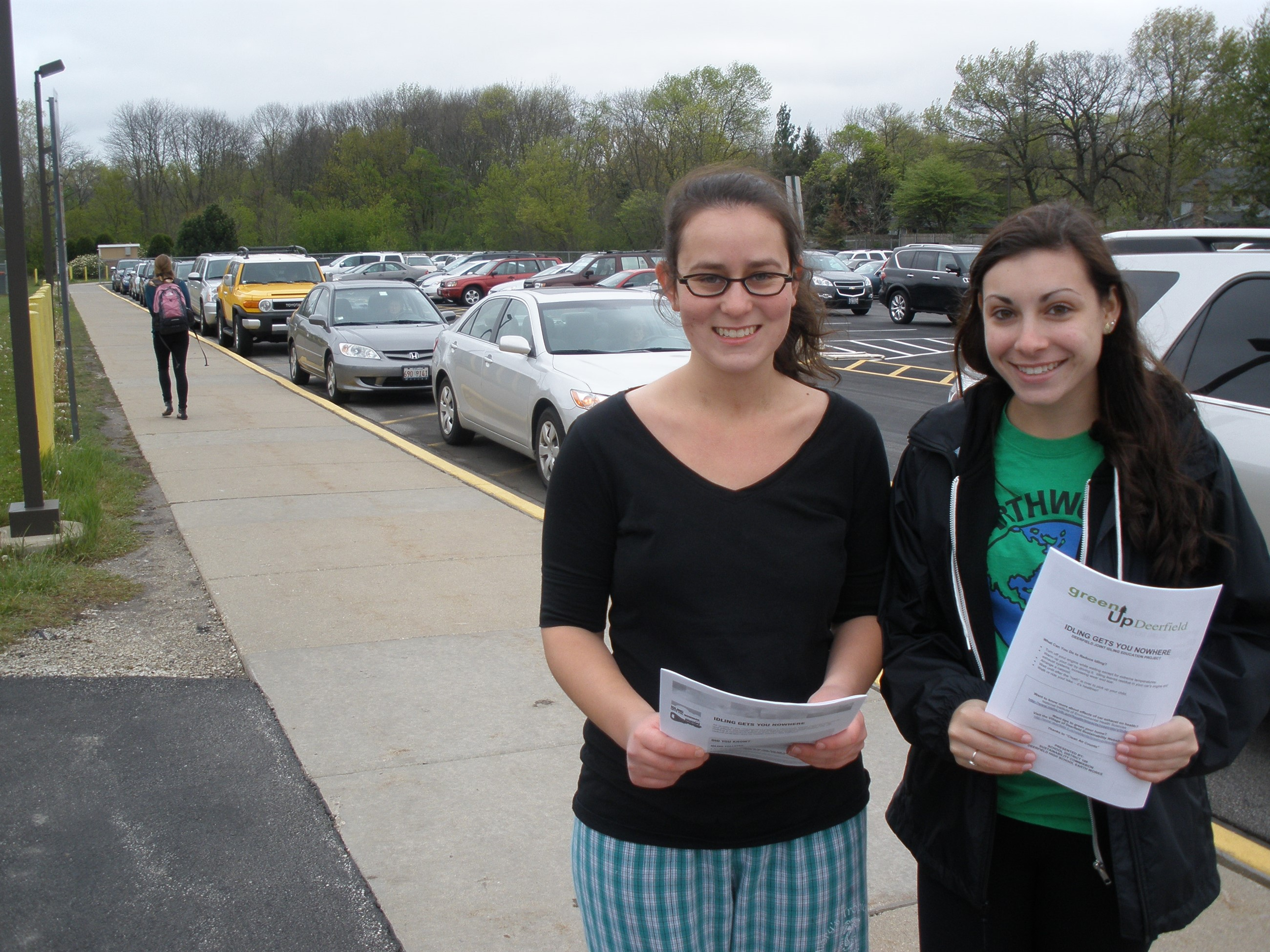 Two girls holding flyers by cars