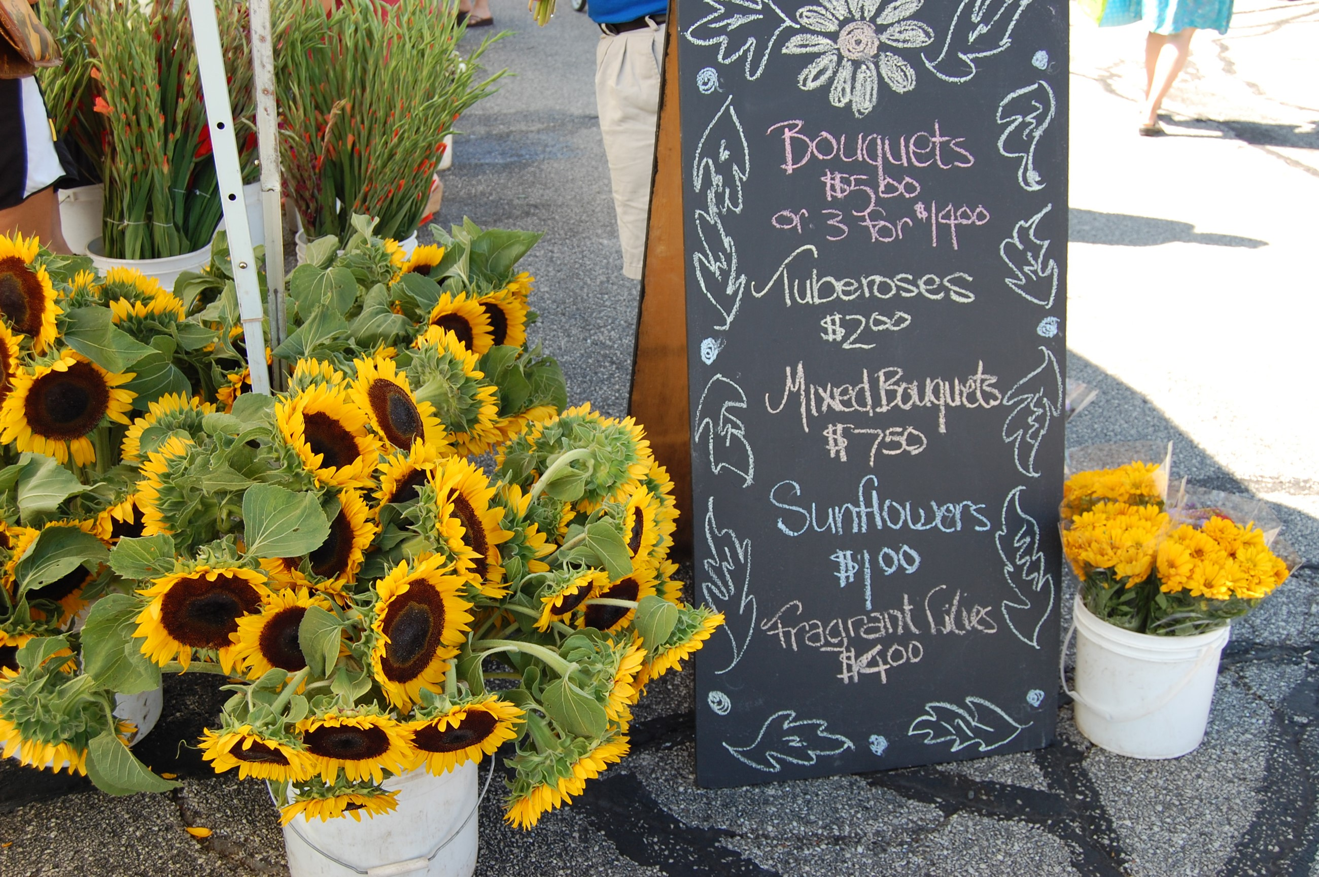 Sunflower bouquet next to market sign