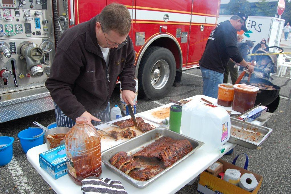 Man plating meat next to a fire truck