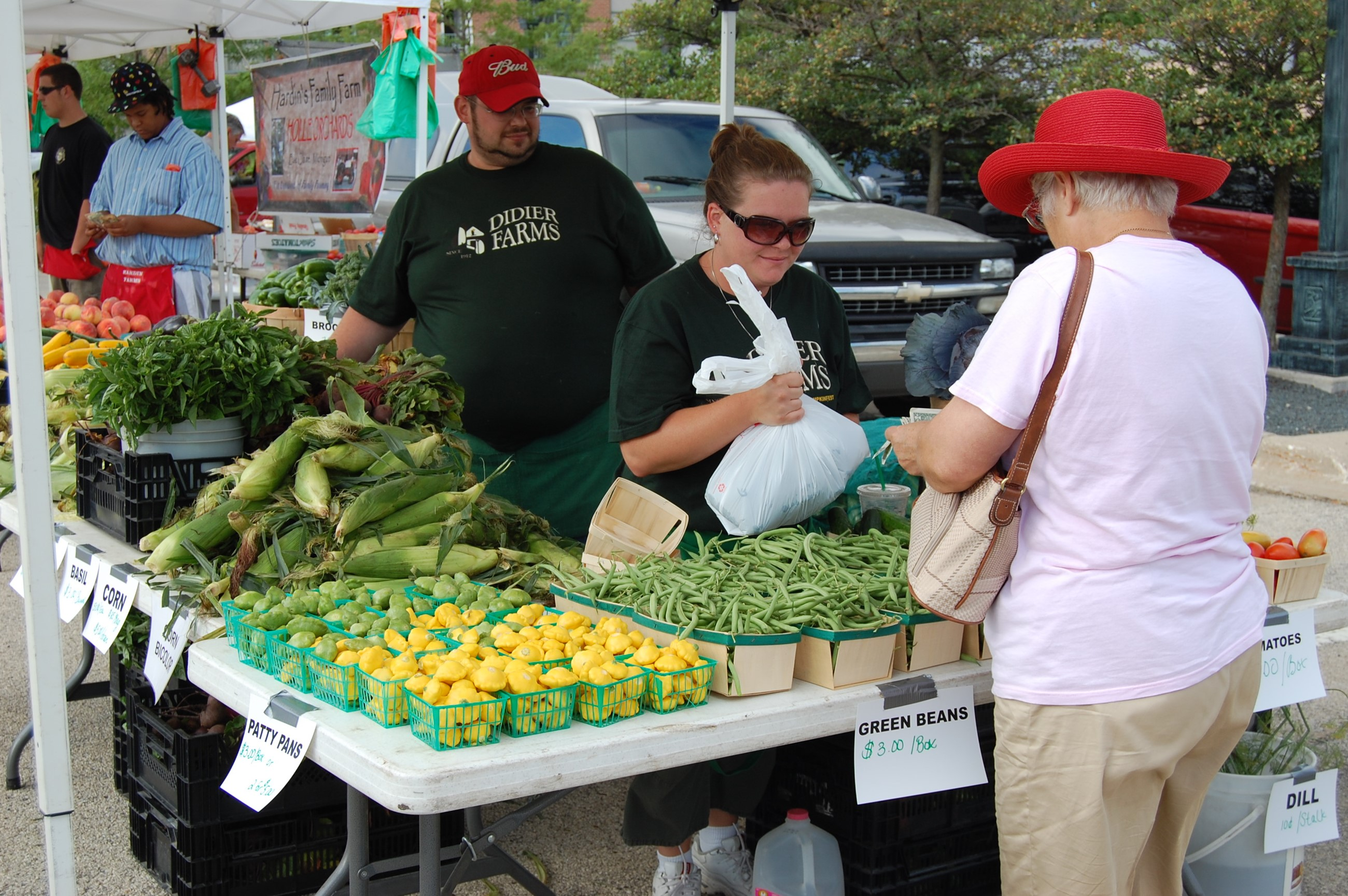 Vendors and customers with yellow and green produce